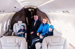 Família que viaja pelo jato comercial do ar Fotografia de Stock