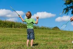 Família - rapaz pequeno que joga o badminton ao ar livre Fotos de Stock Royalty Free