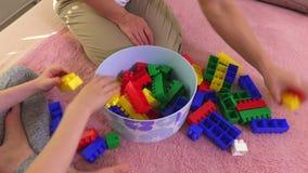 A família recolhe tijolos coloridos do brinquedo vídeos de arquivo