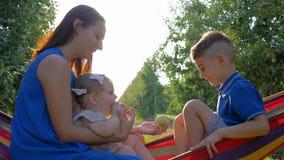 A família rural feliz, fêmea com crianças tem o divertimento que senta-se na rede no jardim da maçã durante a colheita video estoque
