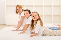 Família saudável feliz que faz exercícios da ginástica Imagem de Stock Royalty Free