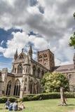 A família senta-se na grama no jardim de Vintry, com a catedral de St Albans no fundo imagem de stock royalty free