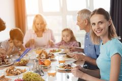 A família senta-se na tabela festiva para a ação de graças A mulher no primeiro plano olha a câmera Foto de Stock