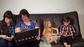 A família senta-se no sofá e usa-se dispositivos digitais video estoque