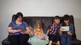 A família senta-se no sofá e usa-se dispositivos digitais vídeos de arquivo