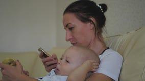 Família, tecnologia, maternidade e conceito dos povos - mãe feliz com o bebê pequeno que encontra-se no sofá e no smartphone em filme