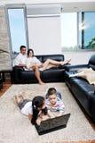 A família tem o divertimento e o trabalho no portátil em casa Fotos de Stock Royalty Free