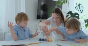 A família tem o divertimento que pinta no papel com seus dedos na pintura A mamã e duas crianças pintam com os dedos no papel video estoque
