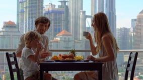 A família tem um café da manhã em um balcão que negligencia os arranha-céus do centro da cidade vídeos de arquivo