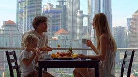 A família tem um café da manhã em um balcão que negligencia os arranha-céus do centro da cidade video estoque