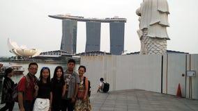 A família toma a foto em areias da estátua de Merlion, da baía do porto e em flor imagens de stock