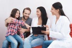 A família veio ver um dentista em uma clínica médica O secretário ajuda a preencher todos os papéis necessários Foto de Stock Royalty Free