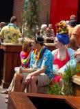 Família vestida na roupa tropical a mulher com fruto em sua cabeça senta-se com outros frequentadores do partido no distrito Kans fotos de stock royalty free