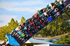 Famílias agradáveis e amigos que apreciam o passeio do roller coaster na área internacional da movimentação imagem de stock