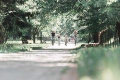 Famílias amigáveis em um passeio da bicicleta no parque da cidade fotos de stock royalty free