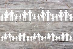 Famílias brancas de papel no fundo de madeira fotos de stock