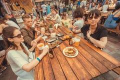 Famílias com as crianças adolescentes que têm o jantar, comendo e bebendo durante o festival exterior do alimento da rua Imagem de Stock Royalty Free