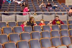 Famílias com as crianças no auditório com rodas pretas fotos de stock royalty free