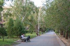 Famílias com as crianças que relaxam no parque em um dia de verão imagens de stock