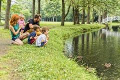 Famílias com crianças perto de um waterscape com o pato nele fotografia de stock