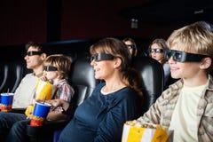Famílias de sorriso que olham o filme 3D no teatro Foto de Stock
