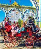 Famílias espanholas no vestido tradicional e colorido que viaja no transportes puxados a cavalo em April Fair, feira de Sevilha foto de stock