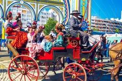 Famílias espanholas no vestido tradicional e colorido que viaja no transportes puxados a cavalo em April Fair, feira de Sevilha fotografia de stock royalty free