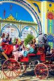 Famílias espanholas no vestido tradicional e colorido que viaja no transportes puxados a cavalo em April Fair fotografia de stock royalty free