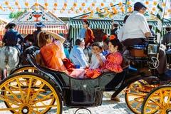 Famílias espanholas no vestido tradicional que viaja no transportes puxados a cavalo em April Fair, feira de Sevilha foto de stock