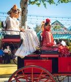 Famílias espanholas no vestido tradicional que viaja no transportes puxados a cavalo em April Fair, Sevilha Feria de Sevilla just foto de stock