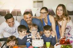 Famílias felizes com as crianças que comemoram em torno de um bolo para um aniversário imagem de stock