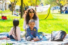 Famílias novas em um piquenique do parque fotos de stock
