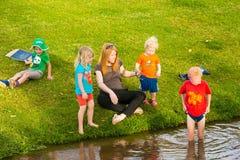 Famílias novas em um piquenique do parque imagem de stock