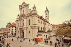 Famílias que andam em torno do mercado e da igreja gótico do século XVIII de Heiliggeistkirche do estilo imagem de stock