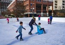 Famílias que apreciam a patinagem no gelo imagem de stock royalty free