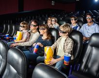 Famílias que olham o filme 3D no teatro do cinema Foto de Stock Royalty Free