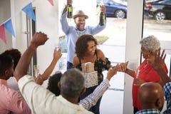 Fam?lia de tr?s gera??es convidados de acolhimento de jogo do partido de surpresa na porta da rua, vista elevado imagem de stock royalty free