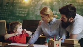 A fam?lia est? fazendo atividades felizes Os pais estão ensinando a criança de tiragem Tração do homem, da mulher e do menino em  filme