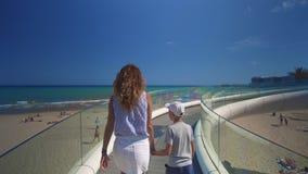Fam?lia feliz ao ar livre caminhada da mãe e do filho perto do mar filme