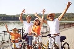 Fam?lia feliz em bicicletas para uma caminhada no parque fotos de stock