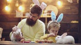 A fam?lia feliz est? preparando-se para a P?scoa Orelhas vestindo do coelho do menino bonito da crian?a pequena P?scoa da pintura video estoque
