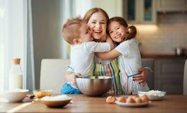 Fam?lia feliz na cozinha a m?e e as crian?as que preparam a massa, cozem cookies foto de stock royalty free