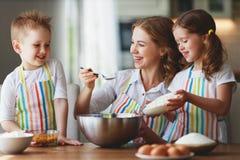Fam?lia feliz na cozinha a m?e e as crian?as que preparam a massa, cozem cookies imagens de stock