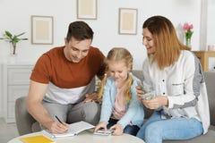 Fam?lia feliz que conta o dinheiro no sof? imagens de stock royalty free