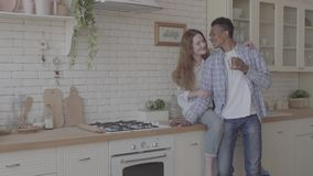 Fam?lia internacional feliz na cozinha que descansa junto Caf? bebendo do homem afro-americano novo, seu caucasiano vídeos de arquivo