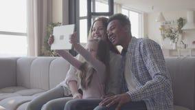 Fam?lia internacional nova bonita em casa, homem afro-americano, mulher caucasiano e menina pequena sentando-se no sof? filme