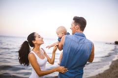 Fam?lia nova bonita em f?rias com beb? O pai guarda a menina loura em seus bra?os, e a m?e da morena abra?a-a foto de stock royalty free