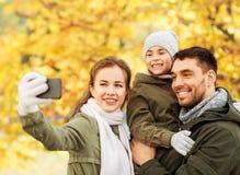Fam?lia que toma o selfie pelo smartphone no parque do outono imagem de stock royalty free