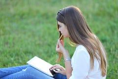 Famale吃快餐的坐的公园和工作膝上型计算机 免版税图库摄影