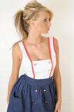 Famale fashion. Young female fashion model standing agaimst a white wall in a studio looking away and up. she is wearing a white top and blue skirt that is high Stock Images